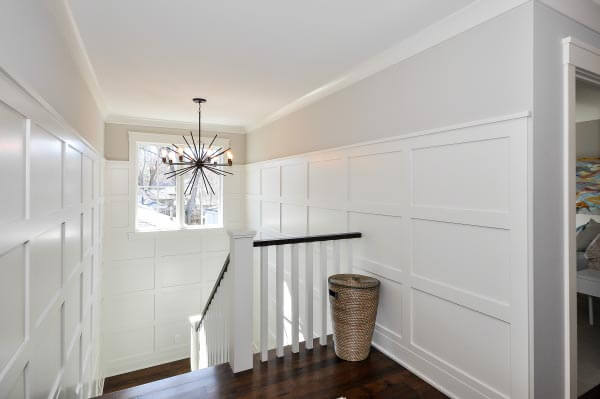 Details like the ten-foot high wainscot and mid-century inspired chandelier add personality to this lovely staircase